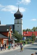 KARPACZ, POLAND - AUGUST 14: Unidentified people and church tower on main str - stock photo