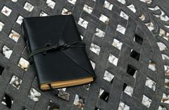 closed leather bound journal on table outdoors - stock photo