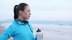 Slow motion of fit woman drinking water on beach after run Stock Footage