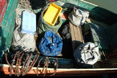 Bags with nets and other thing on small and old fishing vessel. Stock Photos