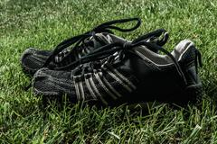 Pair of Black Sport Shoes on Grass Field Stock Photos