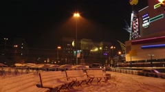 Night city skyline with snowy benches, buildings and the falling snow. - stock footage