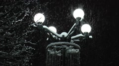 Park street light illuminating the falling snow. - stock footage