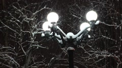 The streetlight with round lamps lighting the falling snow. Stock Footage
