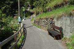 Grindelwald, Switzerland - August 19, 2014: Narrow tarmac footpath and wooden - stock photo