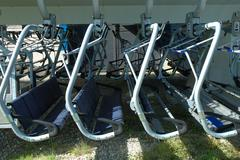 Empty chairlift seats hanging close to each other. - stock photo