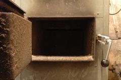Old oven's open door in old boiler room - stock photo