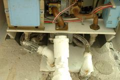 Gas and water pipes connected to heating device Stock Photos