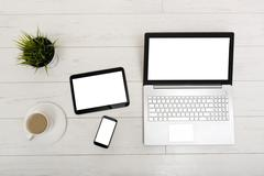 Mock up on a table with laptop, tablet, smartphone and a cup of coffee Stock Photos