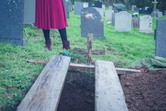 Open grave with woman Stock Photos