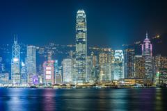 The Hong Kong skyline at night, seen from Tsim Sha Tsui, in Kowloon, Hong Kon - stock photo