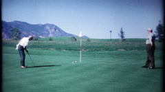 Golfers on green, just miss their putts - 3155 vintage film home movie Stock Footage