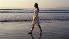 Side view of beautiful woman walking on wet sea shore at sunset - stock footage
