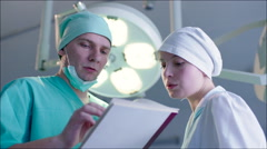 Doctor and Nurse Discussing Case Record - stock footage