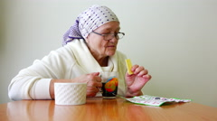 Elderly woman sitting at a table drinking tea and looking Journal Stock Footage