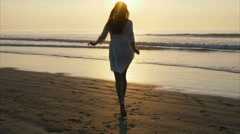 Carefree woman in barefeet running towards sea during sunset Stock Footage