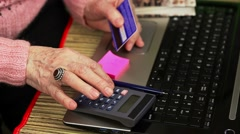 Elderly woman in pink jumper with calculator to counting near laptop Stock Footage