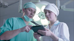 Three doctors using a tablet in a bright office - stock footage