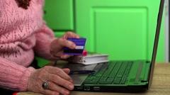 Elderly woman in pink jumper shopping in online Stock Footage