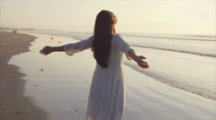 Rear view slow motion video of woman standing with arms outstretched on shore Stock Footage