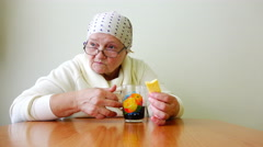 Old elderly sitting at a table with glasses and scarves and drinking tea alone Stock Footage