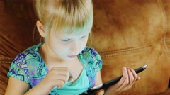 Funny blonde girl playing on the tablet home Stock Footage