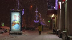 Evening street in a festive Christmas illuminations in heavy snowfall. Stock Footage