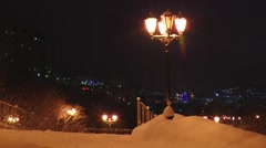 Street lamp in the snowy park in the background the city at night. Stock Footage