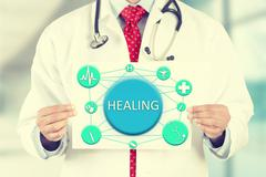 Doctor hands holding white card sign with healing text message Stock Photos