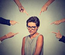 Sad embarrassed woman in glasses looking down many fingers pointing at her Stock Photos