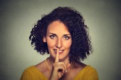 happy young woman placing finger on lips asking shhhhh, quiet, silence - stock photo