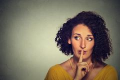 Closeup portrait secretive young woman placing finger on lips asking shh, qui - stock photo