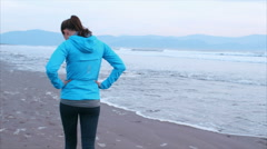Slow motion of fit woman walking with hands on hips at shore after run Stock Footage