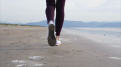 Rear view tracking shot of woman walking on shore Stock Footage