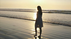 Side view slow motion of young woman walking on wet sea shore at sunset Stock Footage