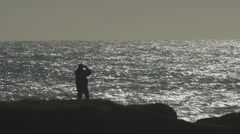 LONE FIGURE SILHOUETTED AGAINST OCEAN VIEW ON BLUFF LOOKING THROUGH BINOCULARS - stock footage