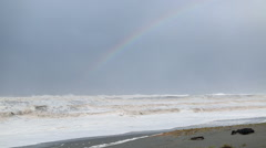 RAINBOW OVER OCEAN WAVES CRASHING ON BEACH - stock footage