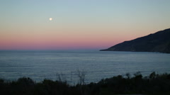 OCEAN DAWN OR DUSK SCENE WITH FULL MOON AND LAND; WIDE Stock Footage