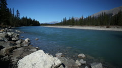 ARTISTIC BLUE GLACIAL RIVER OUT OF FOCUS WITH FOREGROUND ROCK IN FOCUS Stock Footage