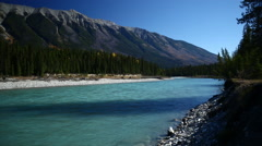 GLACIAL BLUE RIVER FLOWS BY WITH MOUNTAIN IN THE BACKGROUND - 2 Stock Footage
