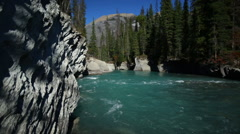 TURQUOISE BLUE RIVER FLOWS BY WHITE GRANITE ROCK Stock Footage