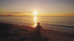 Overhead aerial video of woman standing at beach during sunset Stock Footage
