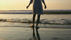 Low section of young woman in barefeet enjoying breaking waves during sunset Stock Footage