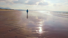 Aerial drone footage of fit woman walking on wet shore Stock Footage