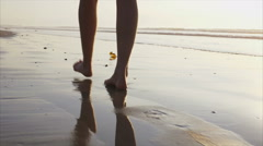 Woman with bare feet walking on wet sand - stock footage