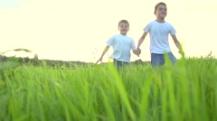 Two happy kids running on summer green field Stock Footage