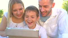 Happy young family with kid using tablet pc in summer park Stock Footage
