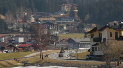 Active traffic on road at mountain bottom, intensive tourist flow to resort town Stock Footage