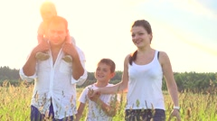 Happy young family with two children walking on summer field Stock Footage