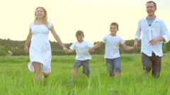 Happy young family with two children running on summer field Stock Footage